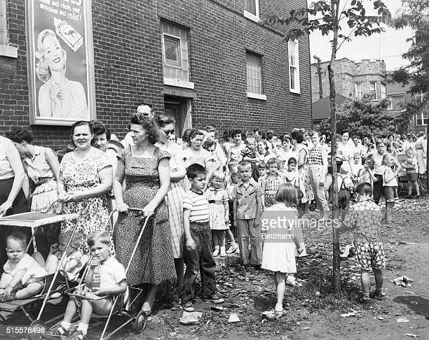 A line of parents and children almost a block long is shown outside a public Health Service Emergency Polio Vaccination Center here 7/16 Chicago has...