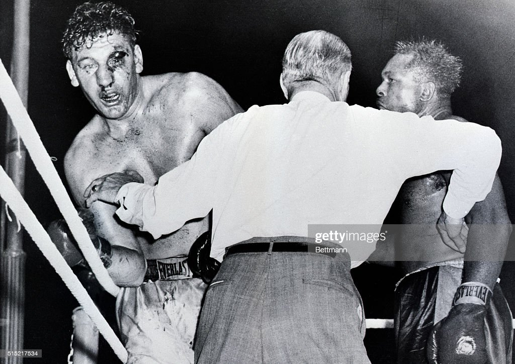 Toronto, Ontario- The badly cut left eye of Canadian heavyweight James J. Parker (L) is seen, as referee Billy Burke holds off <a gi-track='captionPersonalityLinkClicked' href=/galleries/search?phrase=Archie+Moore&family=editorial&specificpeople=93092 ng-click='$event.stopPropagation()'>Archie Moore</a> (R) and stops the fight in the ninth round of their scheduled 15-round bout in the Toronto Maple Leaf baseball stadium. Moore won on a technical knockout.