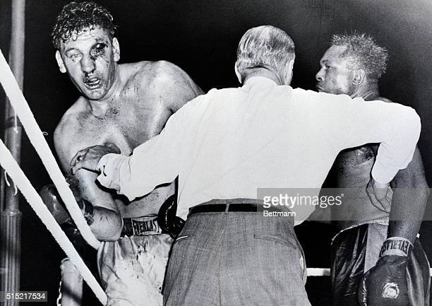 7/25/1956Toronto Ontario The badly cut left eye of Canadian heavyweight James J Parker is seen as referee Billy Burke holds off Archie Moore and...