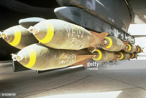 M117 750pound bombs loaded onto the pylon of a B52G Stratofortress aircraft prior to a bombing mission against Iraqi forces during Operation Desert...