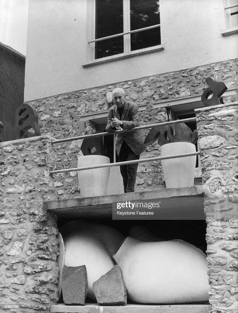 75-year-old French poet, sculptor and painter Jean Arp (1887 - 1966), who helped to found the artistic Dadaist movement, on the balcony of his studio home in the Paris suburbs.