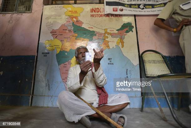 A 75 years old Nageshwar sitting at a polling station after casting his vote at Rajouri Garden on April 23 2017 in New Delhi India Voting for 270...