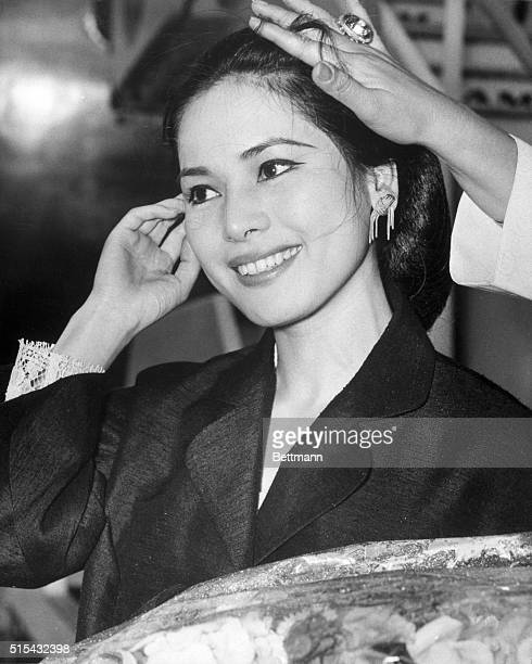 7/6/1965London England Having her hair put back in place by the helping hand of a friend Ratna Sari Dewi Sukarno smiles as she arrives in London The...