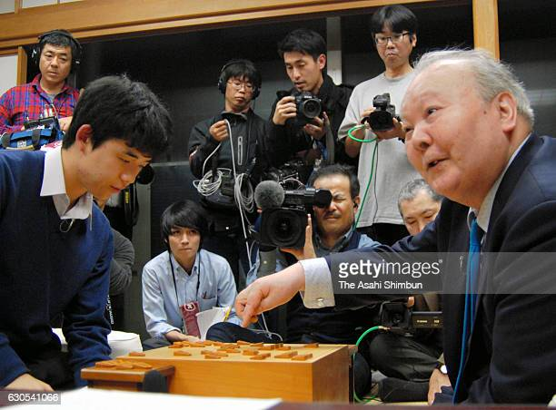 76yearold professional shogi player Hifumi Kato congratulates 14yearold player Sota Fujii after the qualification of the Ryuo Title match at Tokyo...
