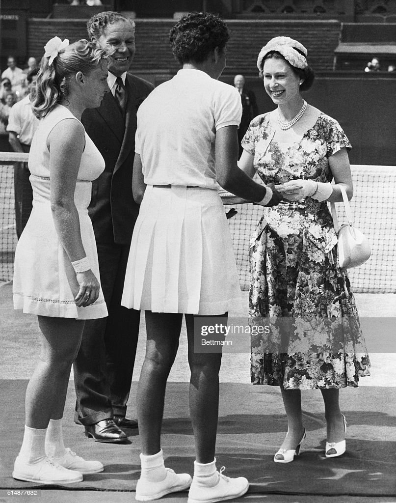 A picture that makes sports history, snapped at Wimbledon, as her majesty Queen Elizabeth of England awarded the Wimbledon trophy, symbolic of the tennis singles championship of the world, to Alethea Gibson (center, back to camera), the U.S. star and first Negro ever to take the title, at left, is the unsucessful finals openent, Miss Darlene Hard. Althea beat Darlene in straight sets, 6-3 and 6-2.