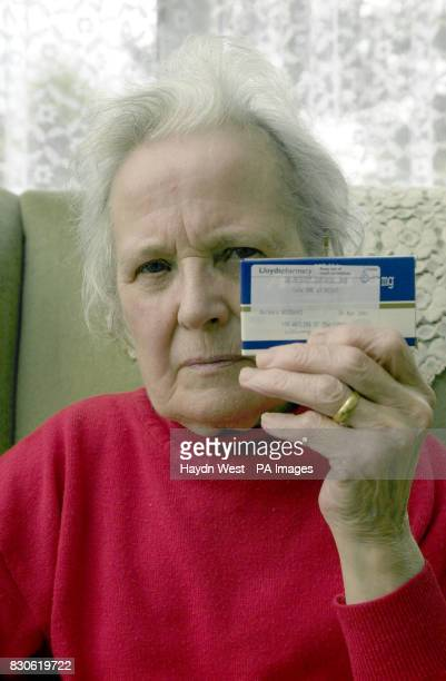 79yearold Barbara Woodward holds her 'Aricept' drugs for Alzheimers disease at the home she shares with her husband Thomas in Shutlanger...