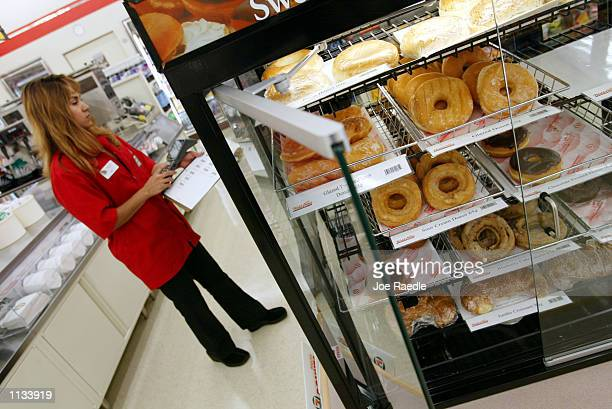 Eleven sales clerk Liz Ramos does an inventory on the cookies and donuts on July 18 2002 in Pembroke Pines Florida 7Eleven Inc the premiere name and...
