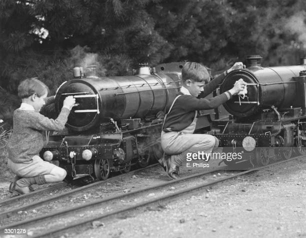 Two boys cleaning model steam engines on Captain Horder's model railway at Buckler's Hard Hampshire
