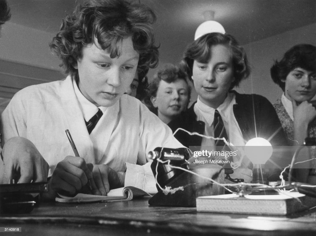 Fifth and sixth form pupils at Cleckheaton Grammar School in Yorkshire carry out a physics circuitry experiment with a lightbulb. Original Publication: Picture Post - 8306 - The Cold War Can Be Won In The Classrooms - pub. 1956