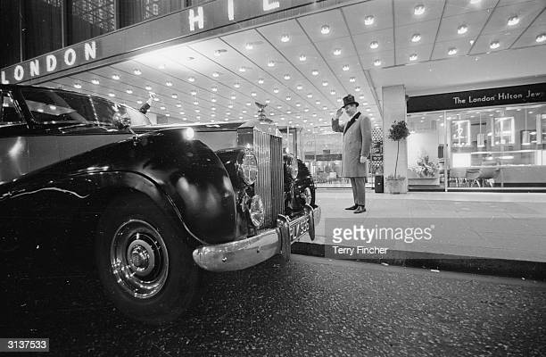A doorman salutes a guest arriving at the Hilton Hotel London in a Rolls Royce