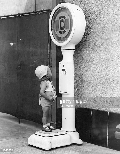 A fat conscious toddler on hodiday has her weight checked on a weighing machine