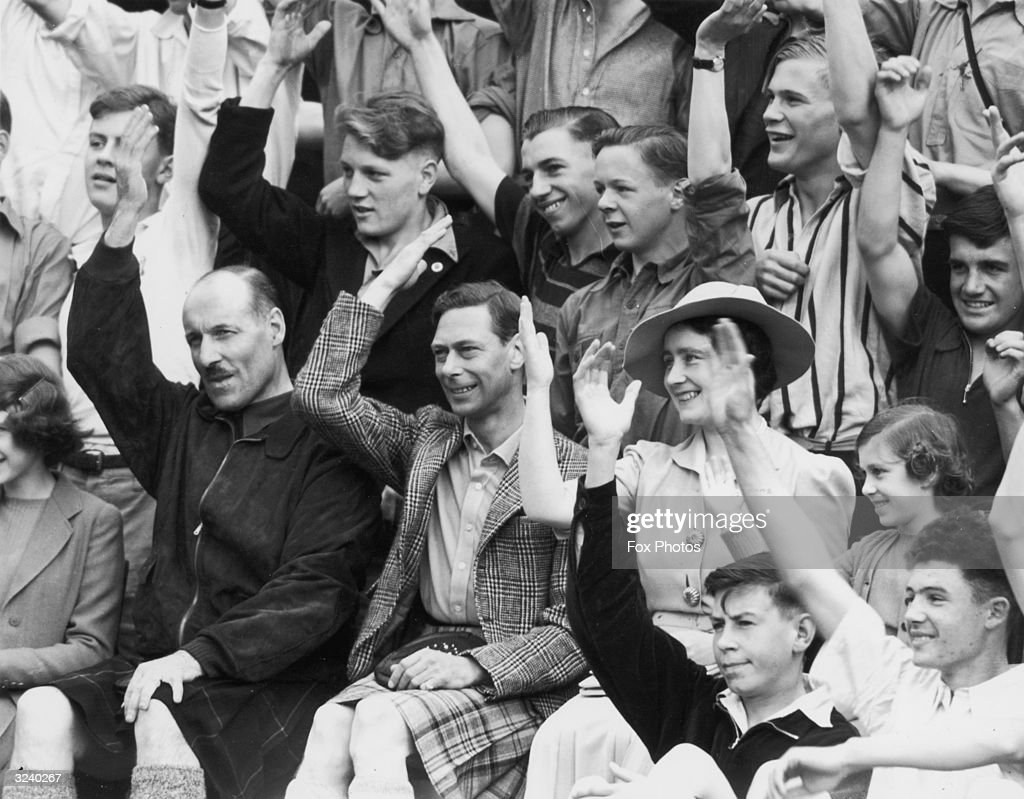 King George VI and Queen Elizabeth joining in with a song during a visit to the King's Camp at Abergeldie Castle near Balmoral. Princess Margaret (1930 - 2002) sits next to the Queen and Princess Elizabeth is on the far right.