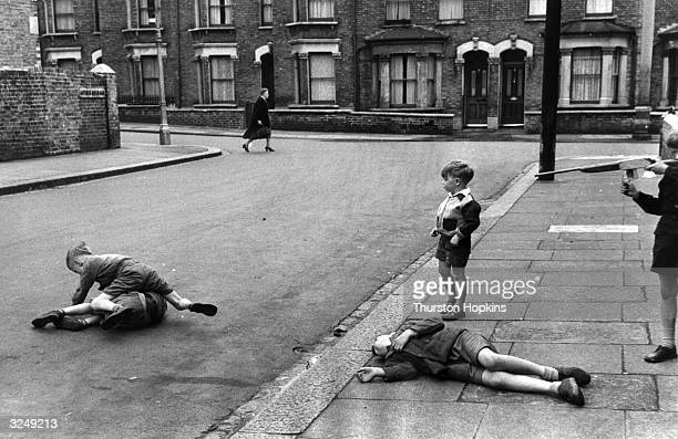 A group of boys play war games in a city street Original Publication Picture Post 7230 Children Of The Streets pub 1954
