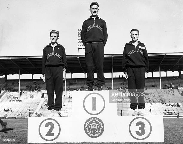 English professional athletes Frank Sando Peter Driver and Jim Peters on the rostrum at the British Empire Games Vancouver Canada after winning...