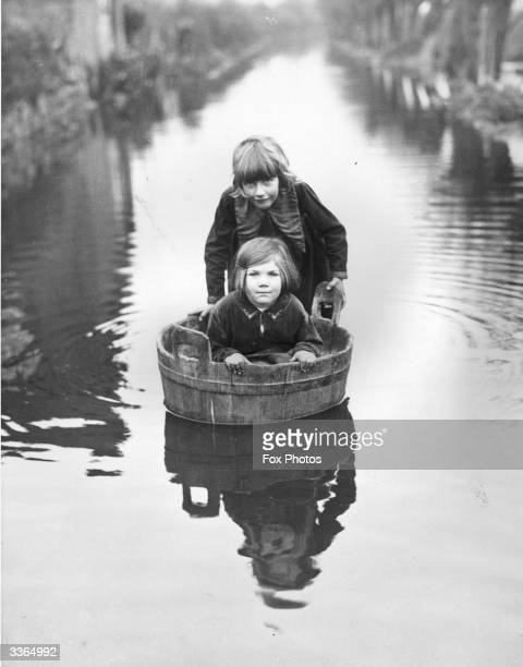 Two young girls using a wash tub as a boat during the floods at Langport Somerset which have prevented them from getting to school