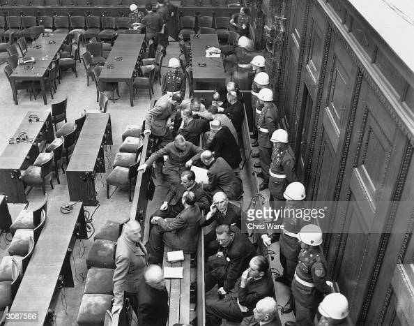 White helmetted soldiers line a courtroom where Nazi leaders listen to the British prosecutor Sir Hartley Shawcross at the Nuremberg WW II Trials