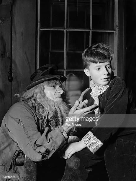Fagin tempts Oliver during a dress rehearsal of the musical 'Oliver Twist' performed by the Dickensian Tabard Players in the courtyard of the George...