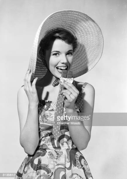 A young woman wearing a large straw hat is enjoying a bar of chocolate