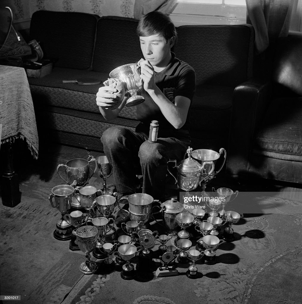 Sixteen year-old Chester Barnes of Essex, the latest winner of the English Closed Table Tennis Championships, polishes his new cup. Around him are about sixty of his other trophies.