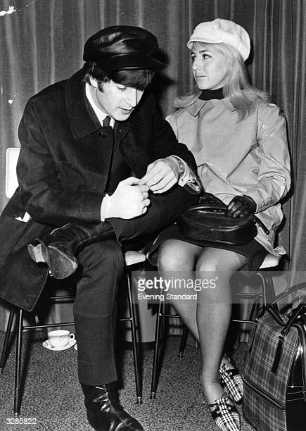 Singer and songwriter John Lennon of British pop group The Beatles and his wife Cynthia wait for a flight to New York at London Airport John is...