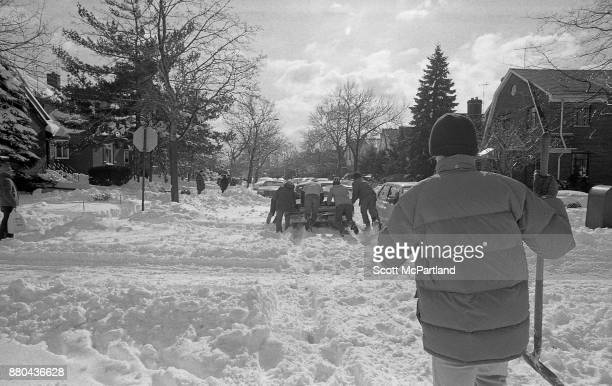 A group of men help push a stranded vehicle through a residential intersection in Queens NY in the aftermath of the Blizzard of 1978
