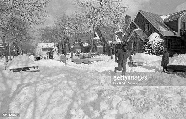 A man runs through deep snow on a residential street as a NYC Sanitation snow plow pulls up behind him in the aftermath of the Blizzard of 1978...