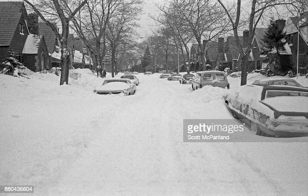 Rows of parked cars sit buried under deep snow drifts on a residential street in Queens NY in the aftermath of the Blizzard of 1978