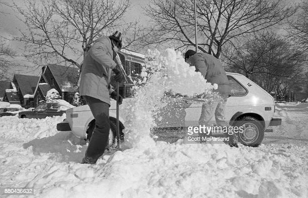 Two men dig out a Volkswagen Rabbit stranded in deep snow in a residential intersection in the aftermath of the Blizzard of 1978