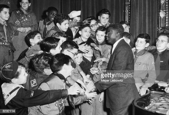 American baseball player Jackie Robinson wearing a business suit standing and smiling as he shakes hands with Boy Scouts and Cub Scouts in uniform at...