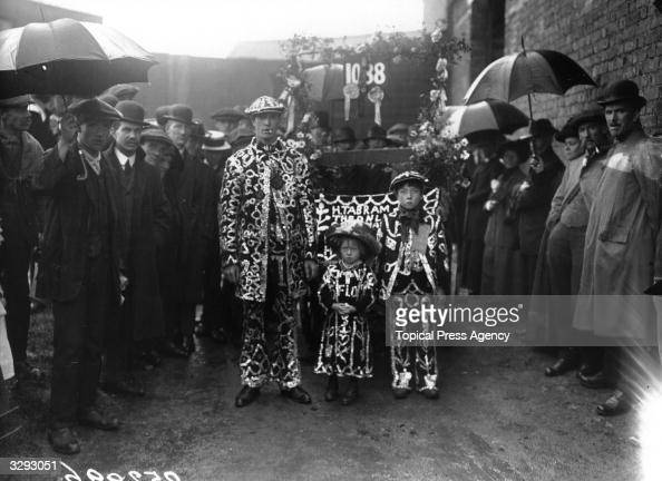 A costermonger in the familiar garb of a Pearly King stands with his similarlyattired children at the South London Costers Donkey Show