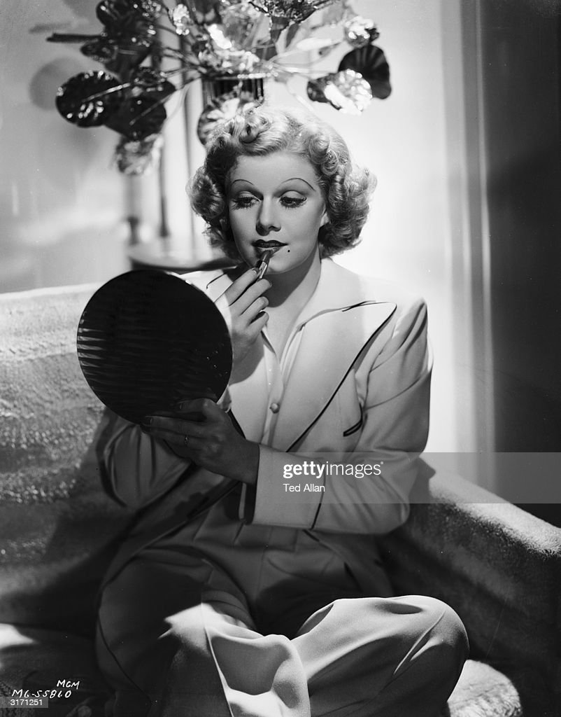 Hollywood star and sex symbol Jean Harlow (1911 - 1937) applying her lipstick.