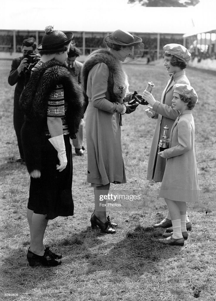 Queen Elizabeth II, then Princess Elizabeth, (right), with her younger sister Princess Margaret Rose (1930 - 2002), are presented with silver replicas of miners' lamps by Mrs Williams and Miss Rees of Cardiff at the Pit Ponies' Display at Windsor.