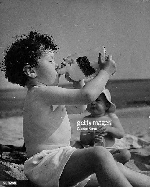 James Shelley drinking milk from an old whisky bottle on Bantham Beach in Devon