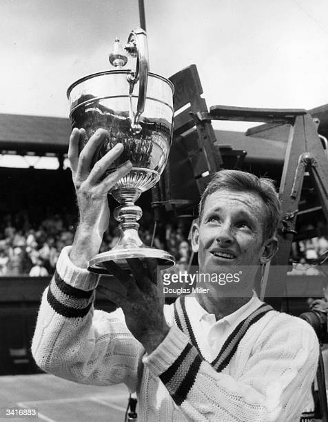 Australian tennis player Rod Laver proudly holding the Men's Singles Trophy at Wimbledon after defeating Chuck McKinley