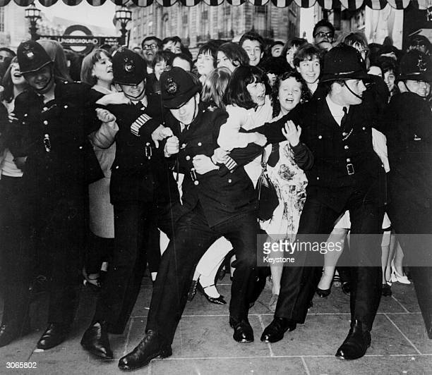 Beatles fans crowded outside the London Pavilion waiting for the band to arrive for the premiere of their first film 'A Hard Day's Night'
