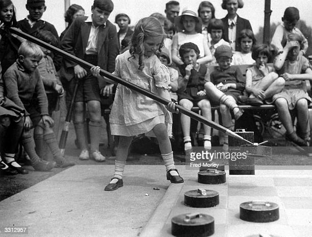 A young girl making her move on a giant open air draughts board in Tottenham London