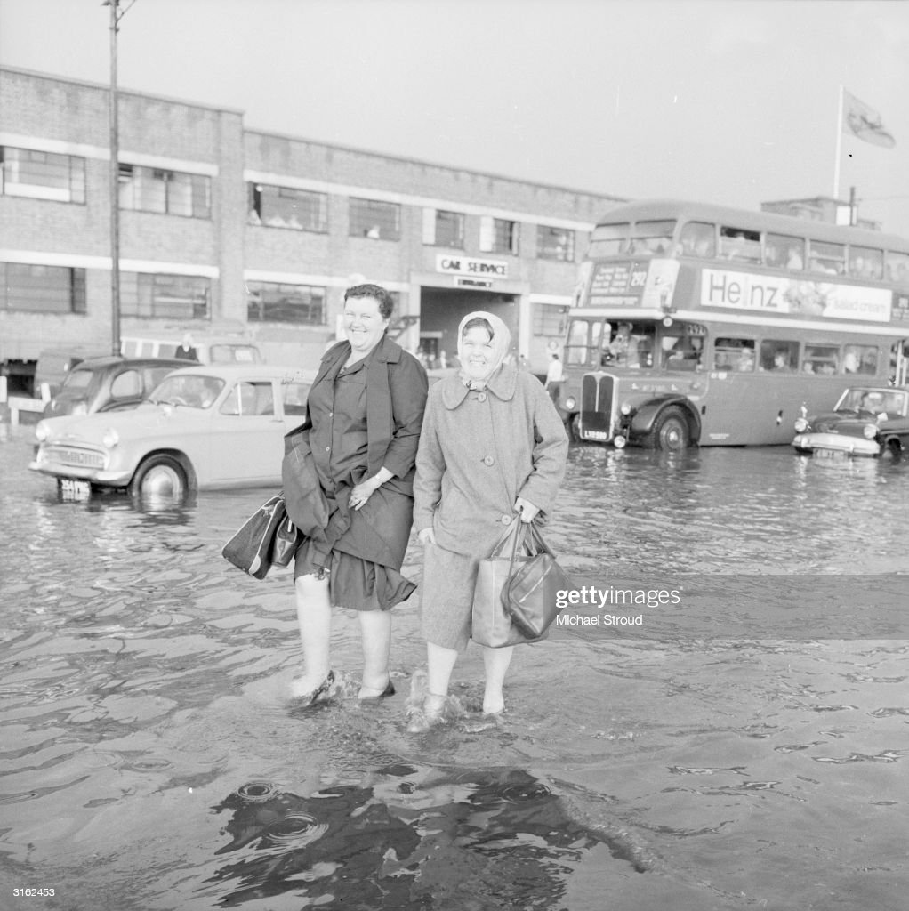Two women wading past stationary vehicles on flooded streets in London.
