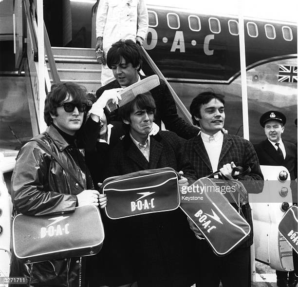 Liverpudlian BOAC air hostess Anne Creech grooms George Harrison's hair with an oversize comb while the Beatles with temporary Ringo replacement...