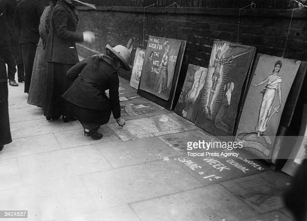 A suffragette adding to messages written by others on a pavement in Kensington