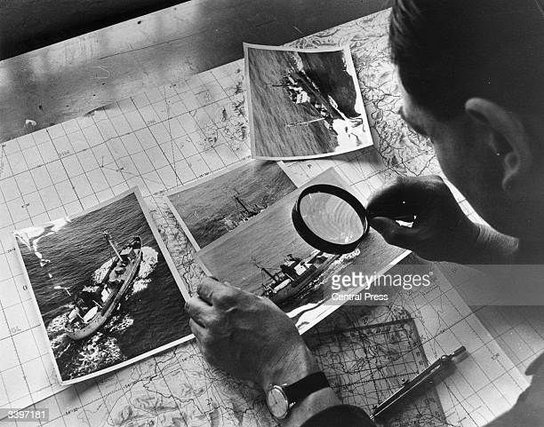 Squadron Leader V A Robins examining photographs of a Soviet spy trawler taken by the RAF during a reconnaissance flight over the Atlantic
