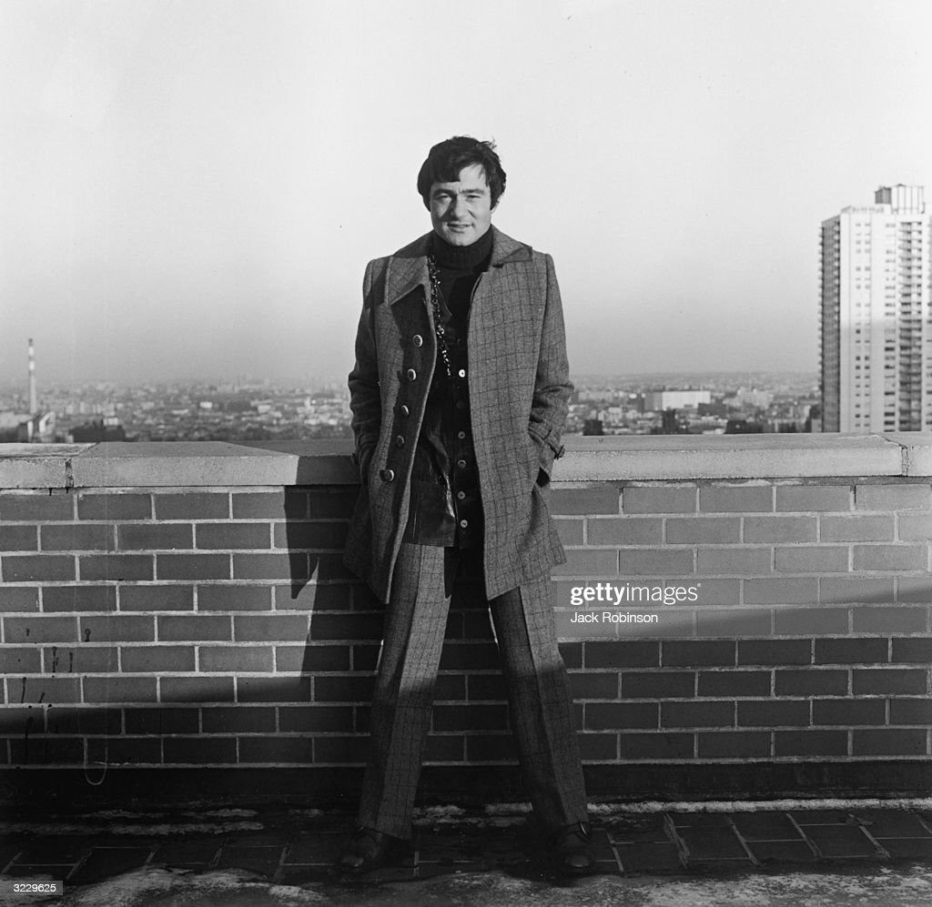 Full-length portrait of British hair stylist Vidal Sassoon posing on the roof of a building in a window pane suit, a leather vest, and chains.