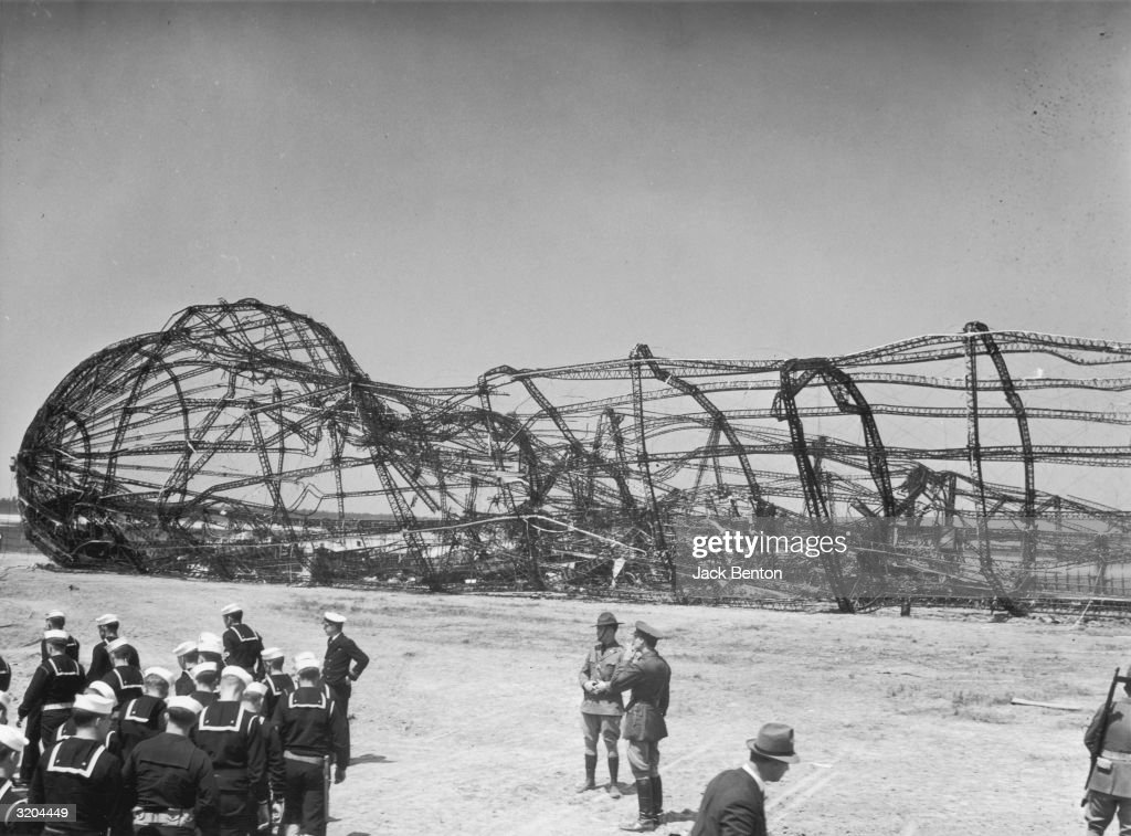 Full-length image of a group of U.S. sailors and several military officers standing in front of the charred frame of the German-made dirigible 'Hindenburg,' the day after it crashed at Lakehurst Naval Air Station, New Jersey. Thirty-six people were killed in the disaster.