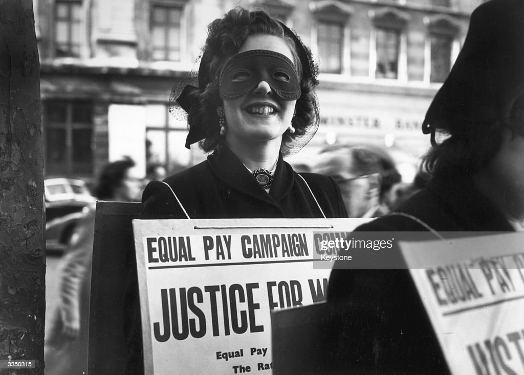 Sonia Banular wears a mask to a poster parade in London demanding equal pay for women.