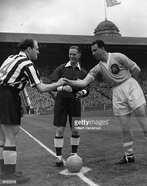Referee Reg Leafe looks on as Newcastle United captain Jimmy Scoular shakes hands with Manchester City captain Roy Paul before the kick off of the FA...