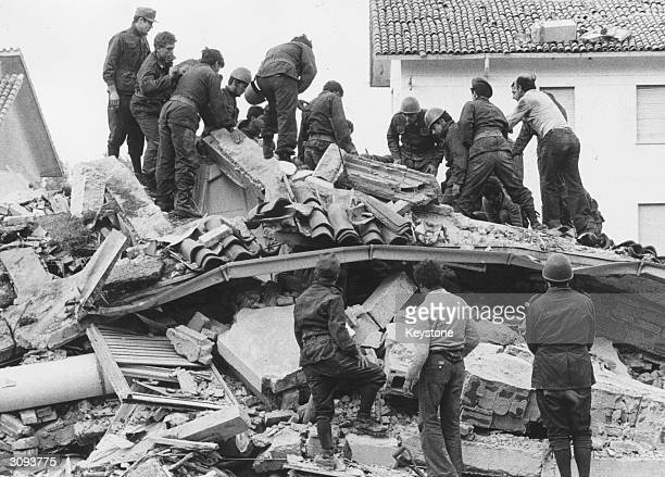 Italian soldiers and civilians trying to dig out bodies from under the debris after an earthquake in the village of Gemona del Friuli killed more...