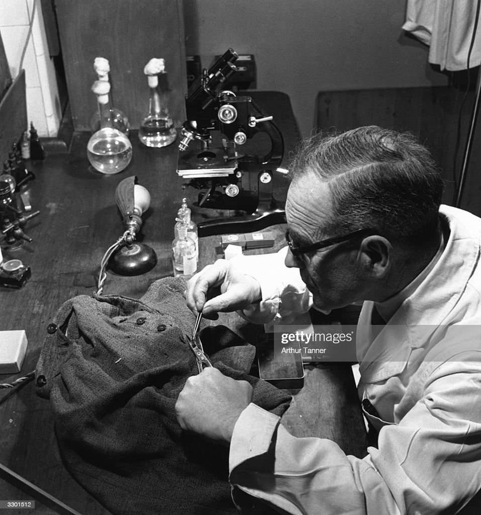 A Scotland Yard forensic scientist analysing the clothing of a hitandrun car crime victim