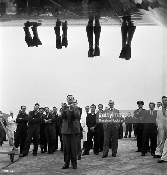 The legs of contestants in a 'Miss World' beauty competition sponsored by Mecca Dancing dangle over the wing of a BOAC Comet much appreciated by...