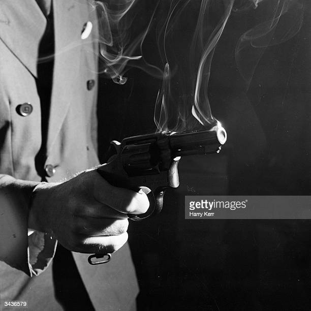 A closeup of the hand of a killer with his finger on the trigger of a smoking gun