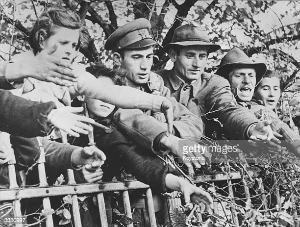 Hungarian refugees leaning over the barriers of Traiskirchen an Austrian refugee camp They are shouting pleas for help to passing pedestrians