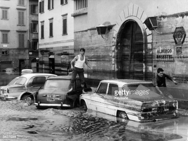 Pedestrians use marooned cars as stepping stones in the flooded streets of Florence after the River Arno had burst its banks
